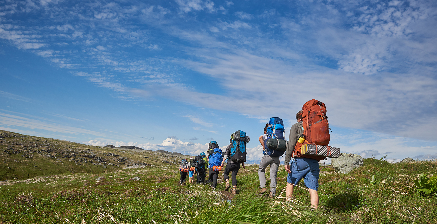 group of camper hiking with backpacks through open field