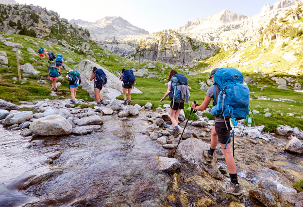 Travelers walking in a line over a stream, all with backpacks