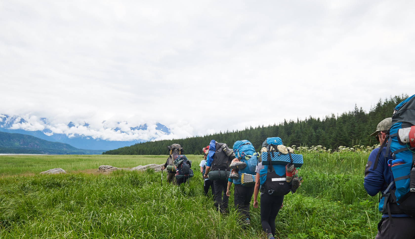 Travelers with backpacks walking in a line