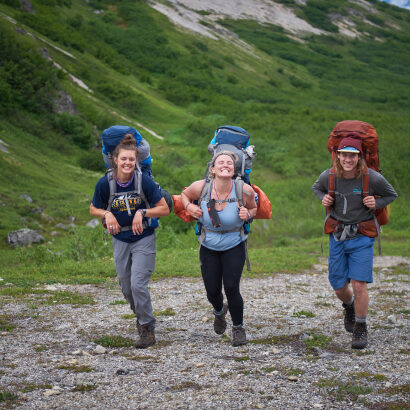 Three travelers with backpacks smiling and walking together