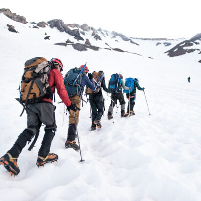 Travelers with backpacks, poles, and shoe spikes, hiking up a snowy mountain