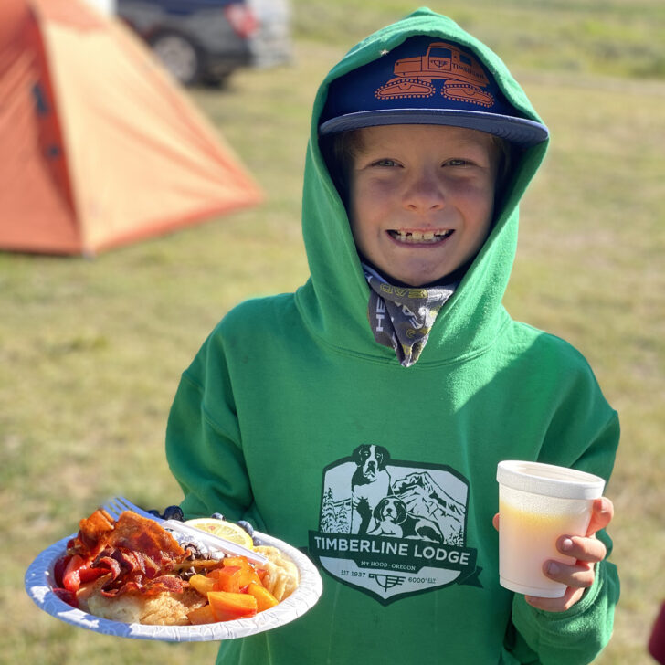 Young kid with plate of food on a campout trip