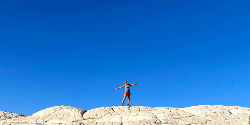 Traveler on top of rocks with arms outstretched
