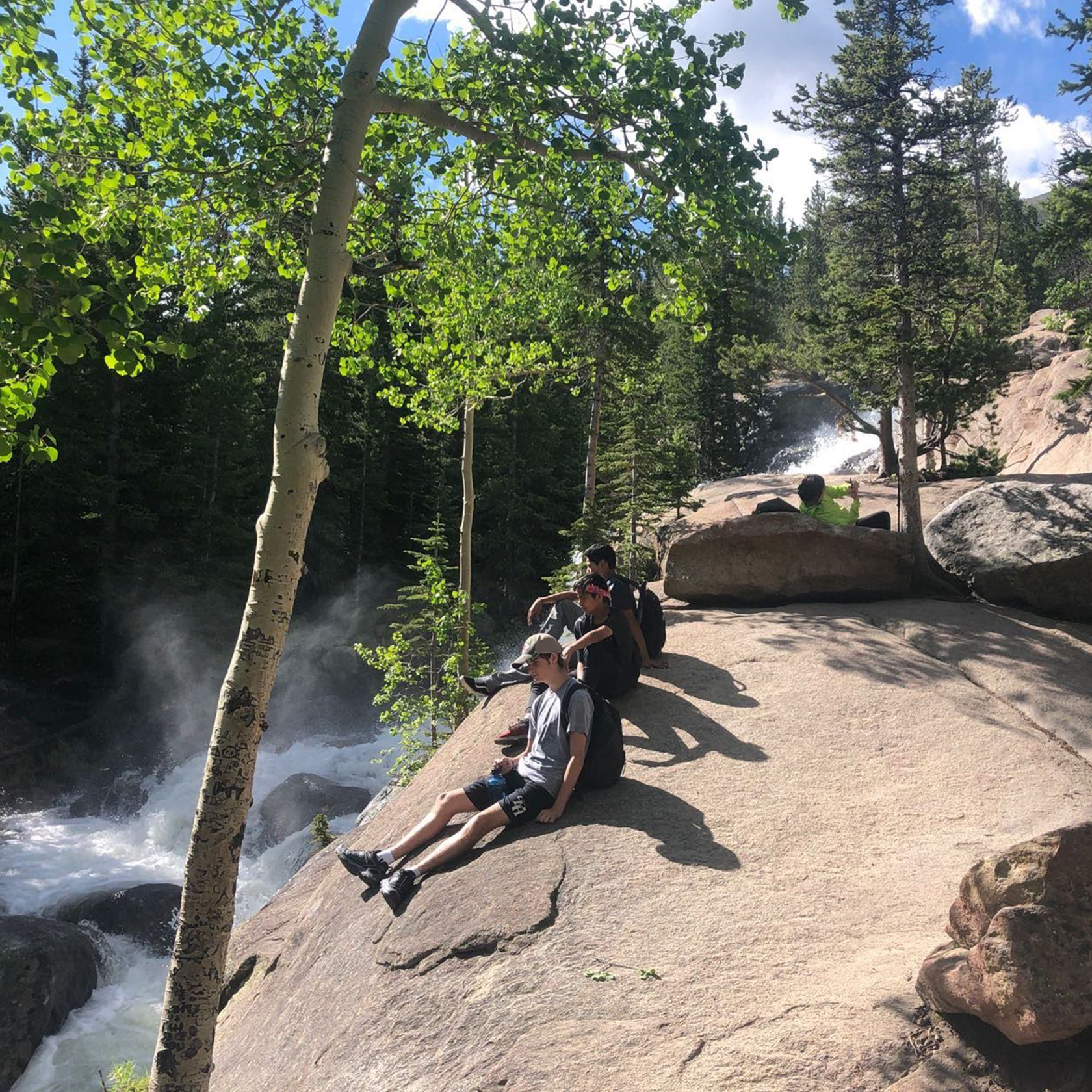 Travelers sitting on rocks above a raging river in The Rockies