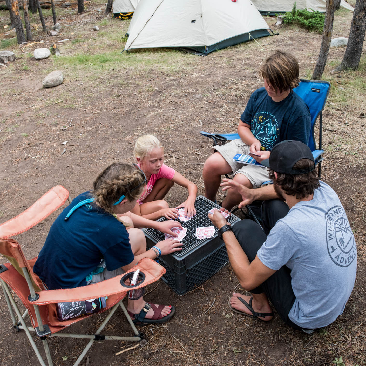 Travelers playing card games at a campsite