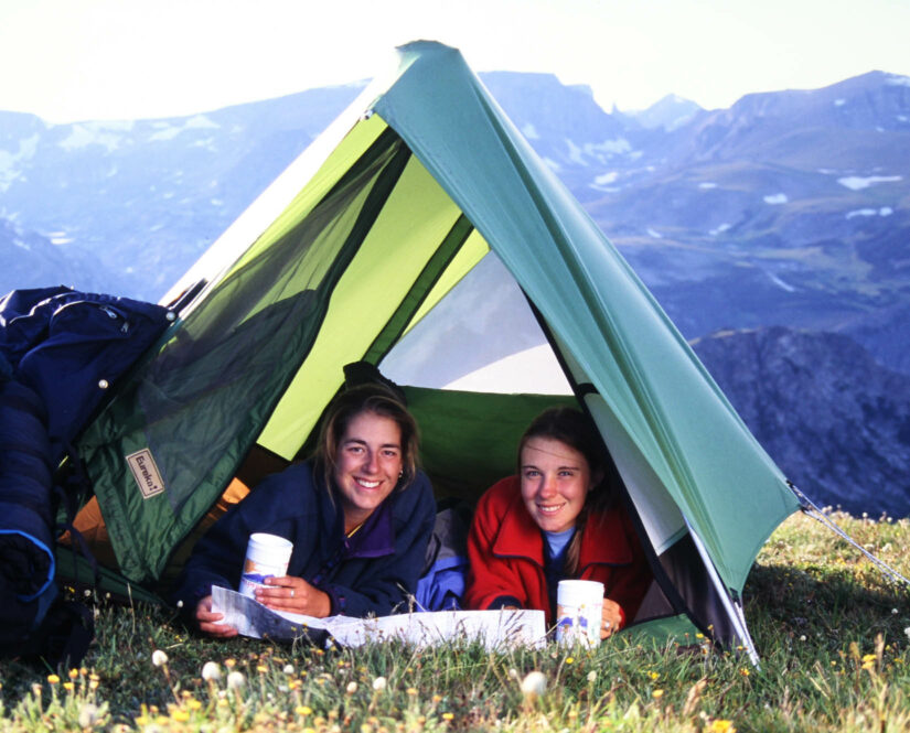 Two girls smiling in their tent