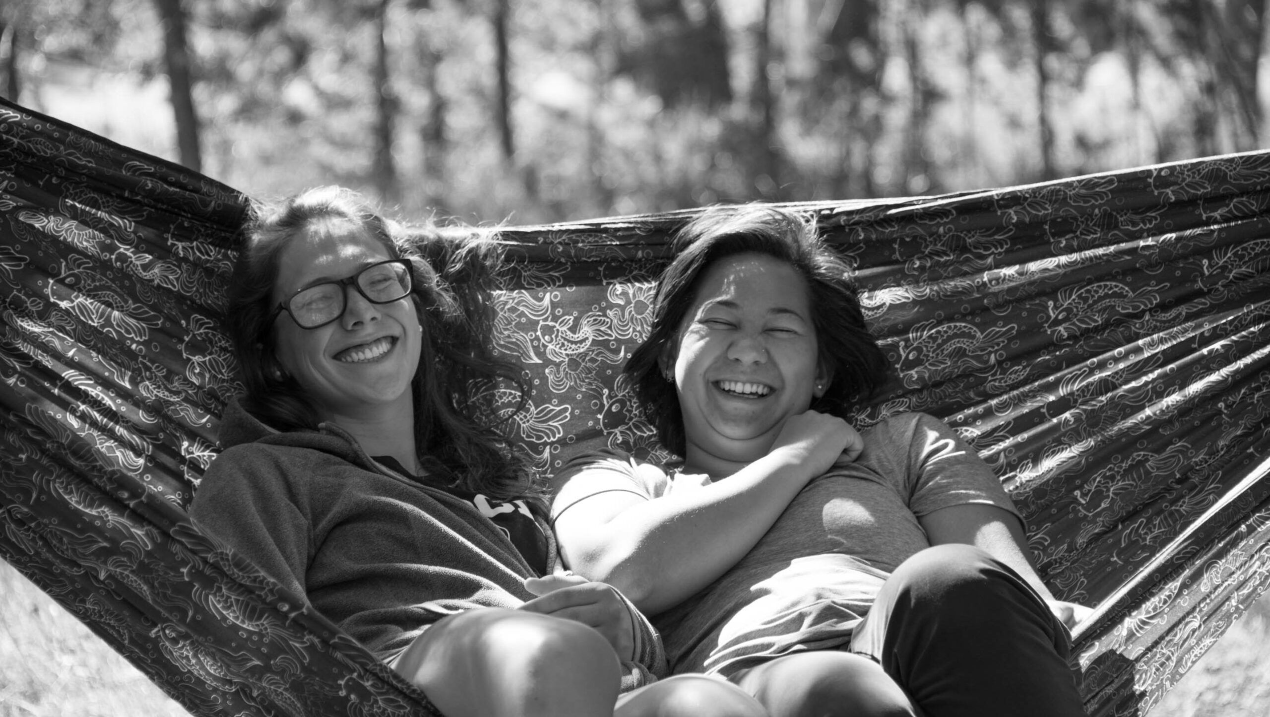 Two girls laughing in a hammock