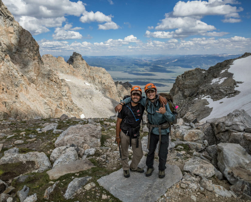 Two travelers at the top of a mountain together