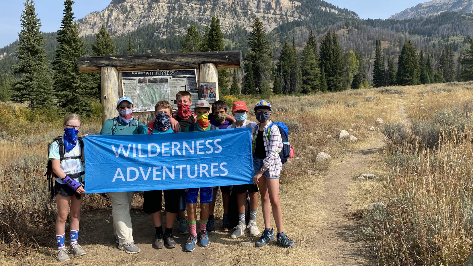 Travel group wearing masks holding a Wilderness Adventures sign