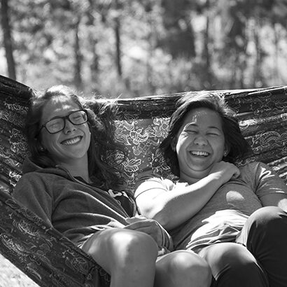 alumni group laughing on outdoor hammock