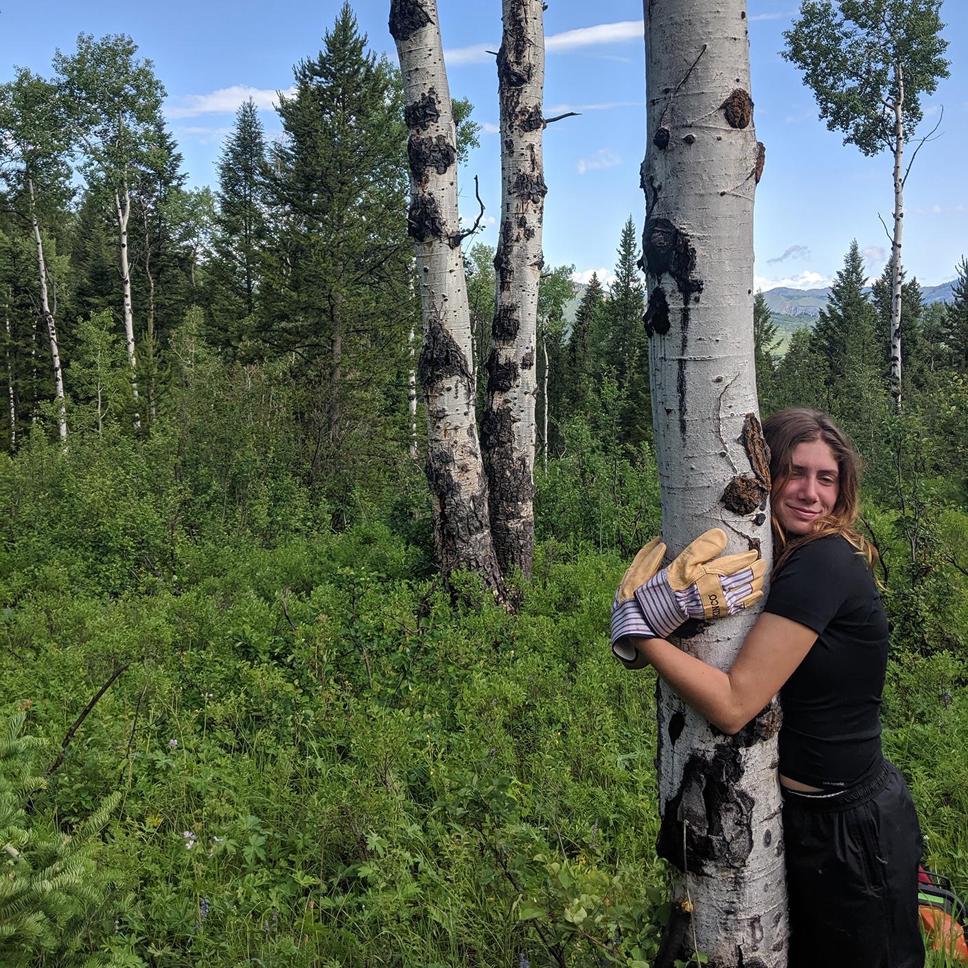 Girl hugging an aspen tree