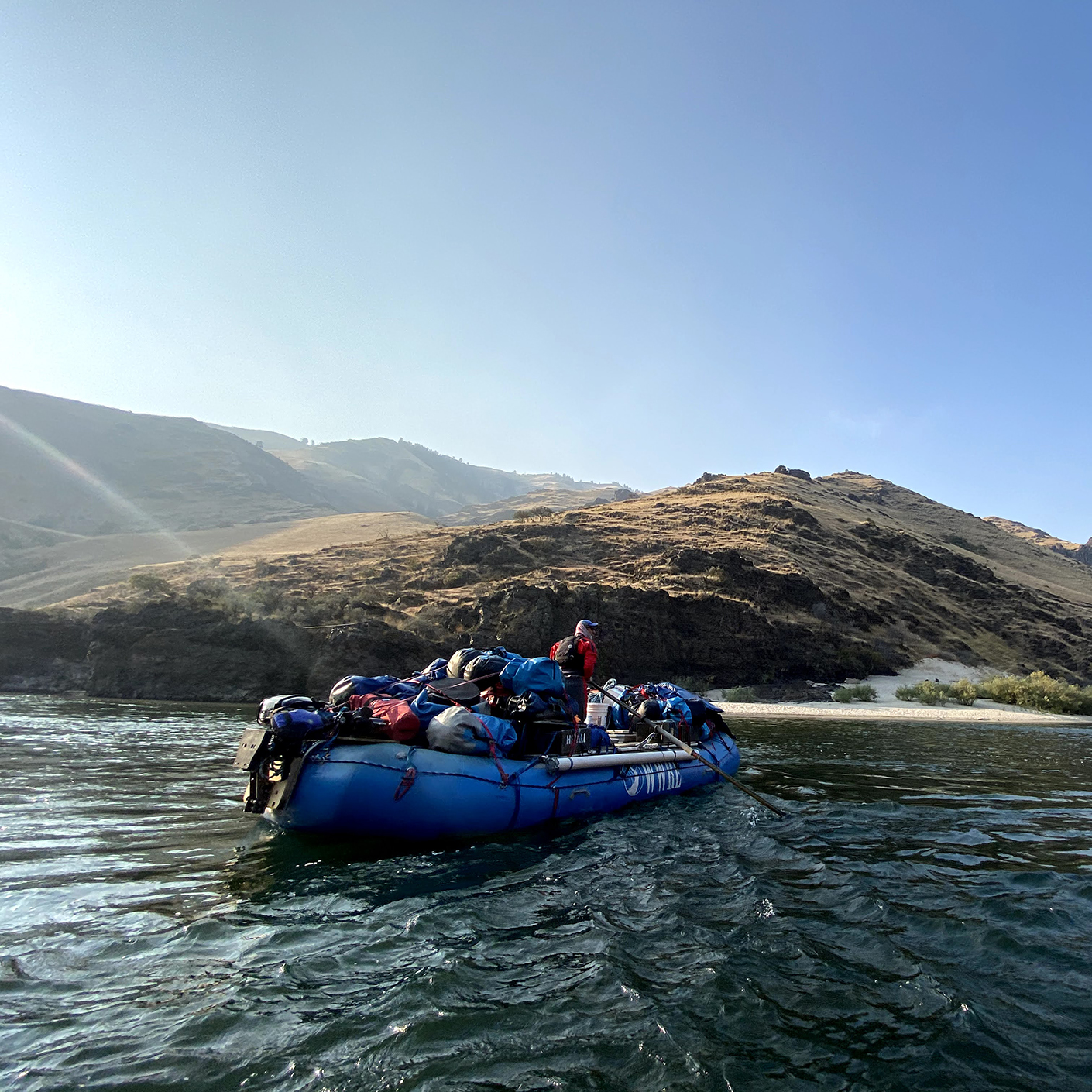 Whitewater rafting guide with loaded boat