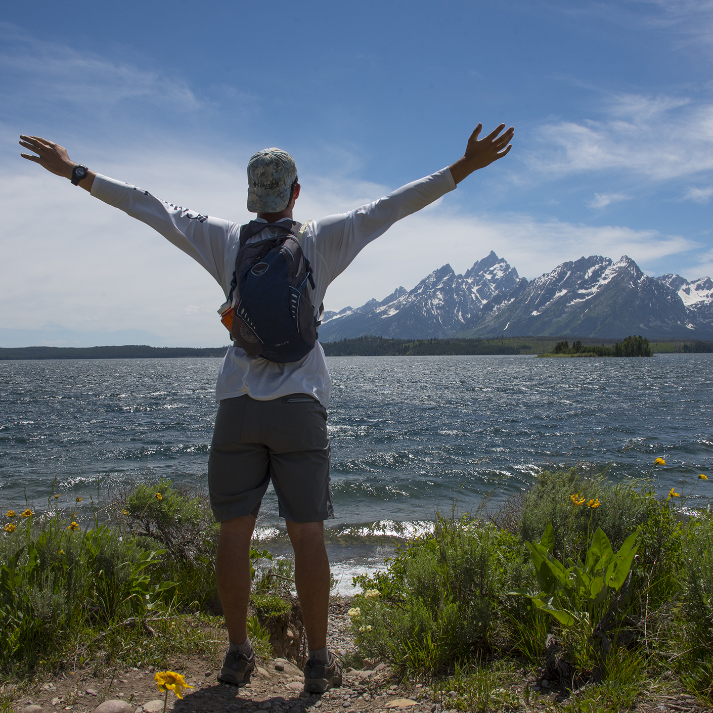 Student with arms up hiking in Grand Teton National Park